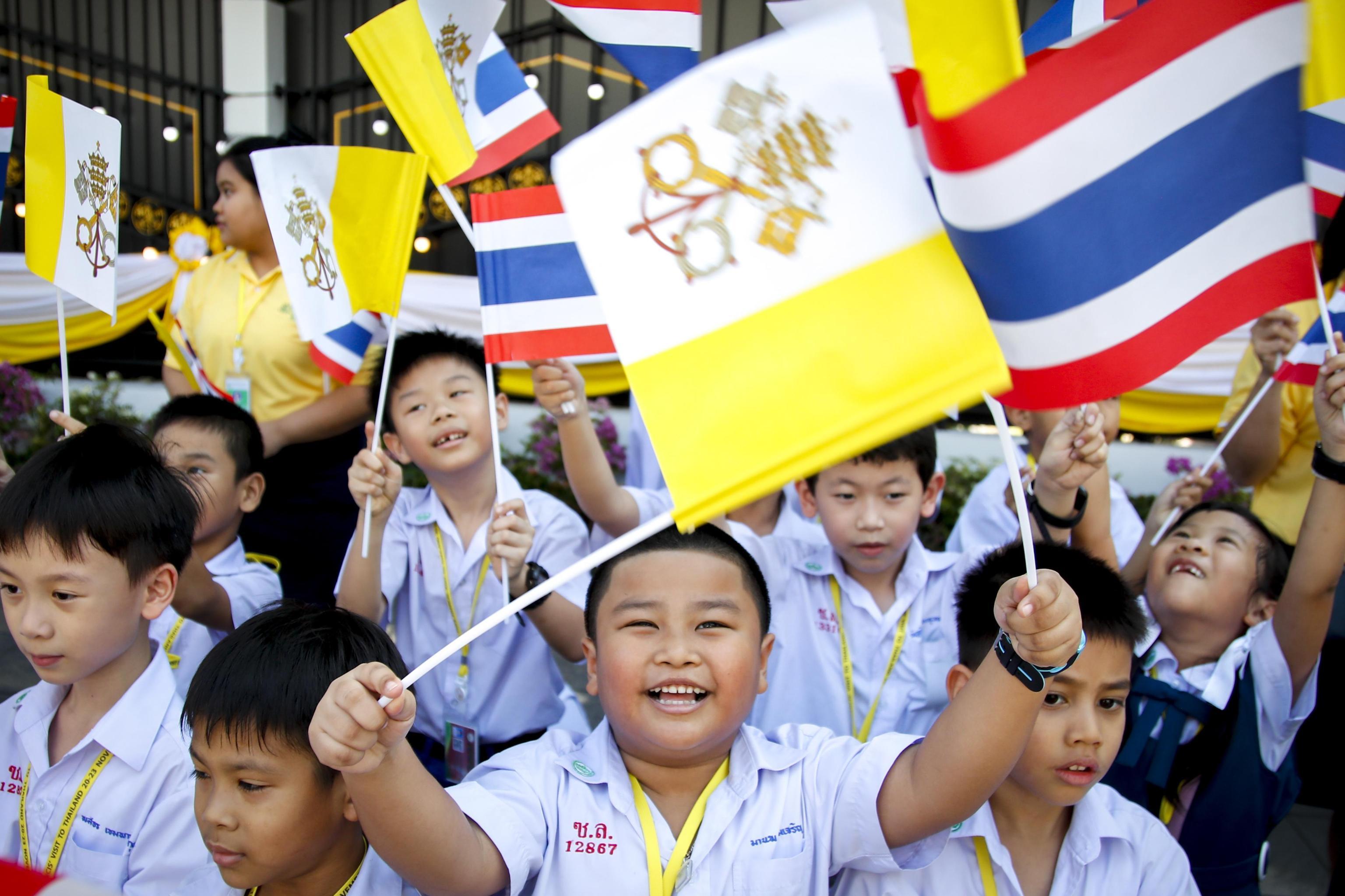 Bambini in festa accolgono il Santo Padre sventolando bandiere del Vaticano e della Thailandia