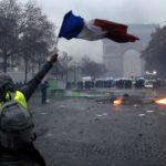 Un manifestante sventola la bandiera francese, sullo sfondo la polizia schierata