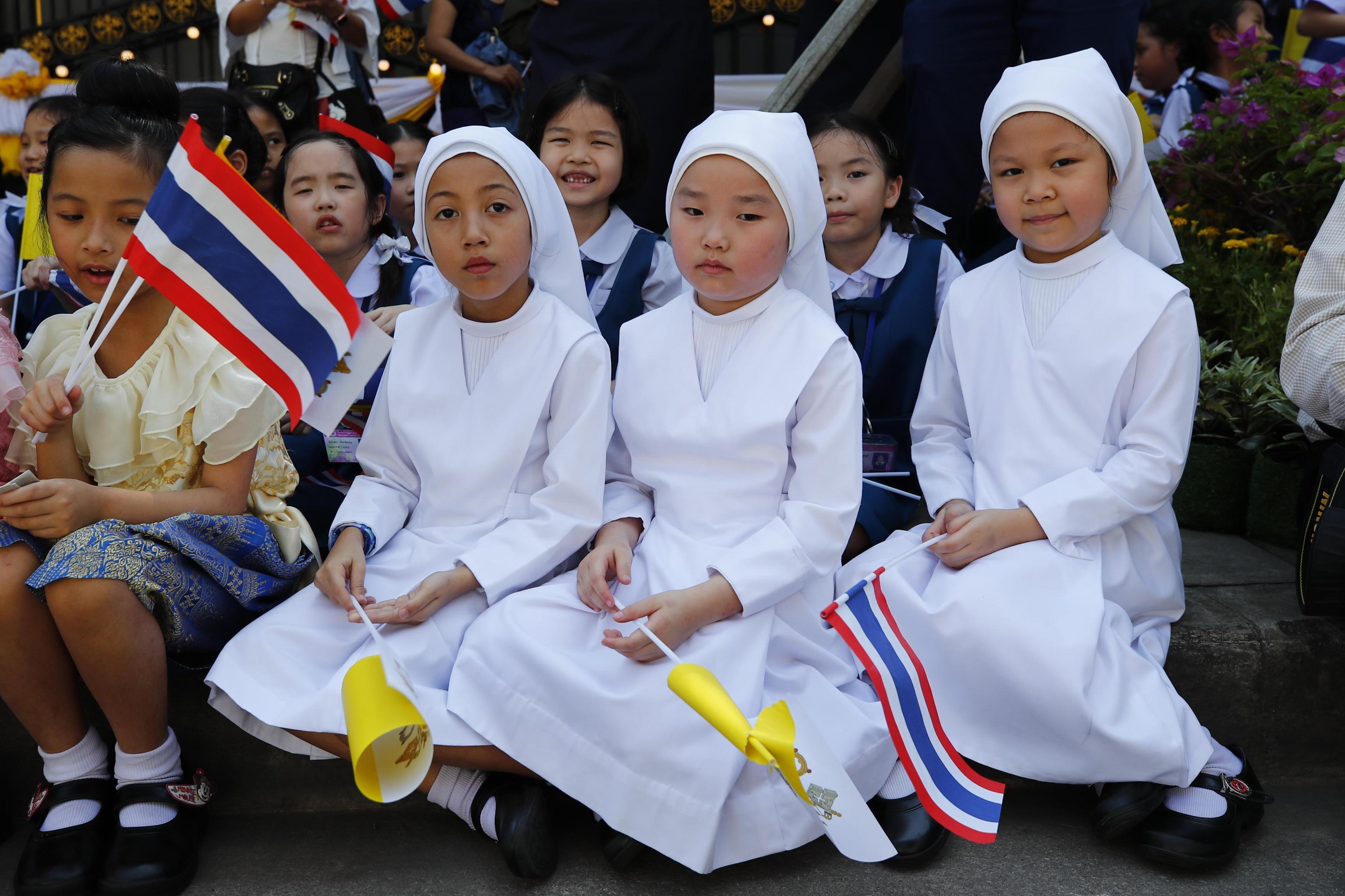 Tre giovani fedeli vestite da suore aspettano di salutare Papa Francesco