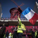 I gilet gialli marciano davanti allo storico Moulin Rouge