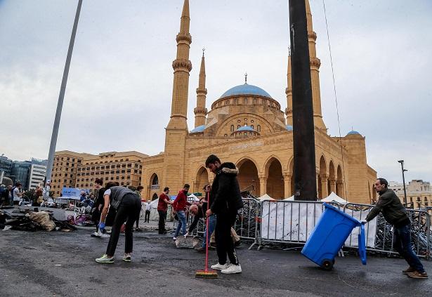 Alcuni volontari ripuliscono l'area della moschea in piazza