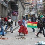 Cittadini boliviani si dirigono a Murillo Square, a La Paz. A terra numerosi detriti dovuti alle recenti proteste che hanno portato alle dimissioni e al trasferimento in Messico dell'ex Presidente Evo Morales. In queste ore la polizia boliviana sta assumendo il controllo delle strade delle principali città del Paese