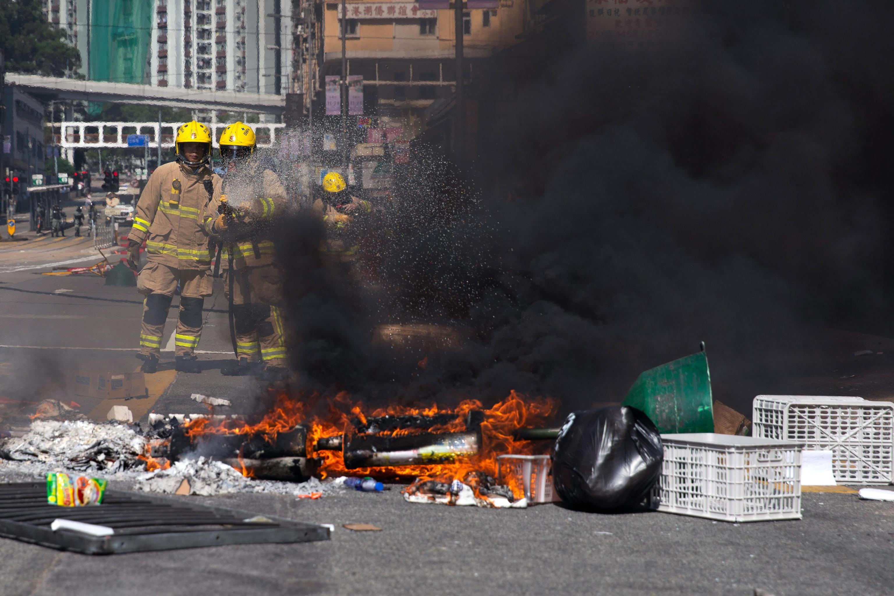La protesta di Hong Kong infiamma tutta la città. Due pompieri alle prese con le barricate date fuoco dai manifestanti