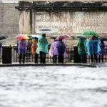 Allerta meteo anche a Roma. Alcuni turisti si riparano dalla pioggia in Campidoglio