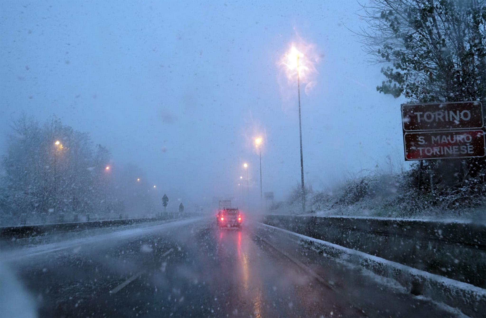 Una strada di Torino dove c'è scarsa visibilità a causa della neve mista a pioggia