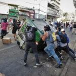 Manifestanti in azione ribaltano un cassonetto dell'immondizia