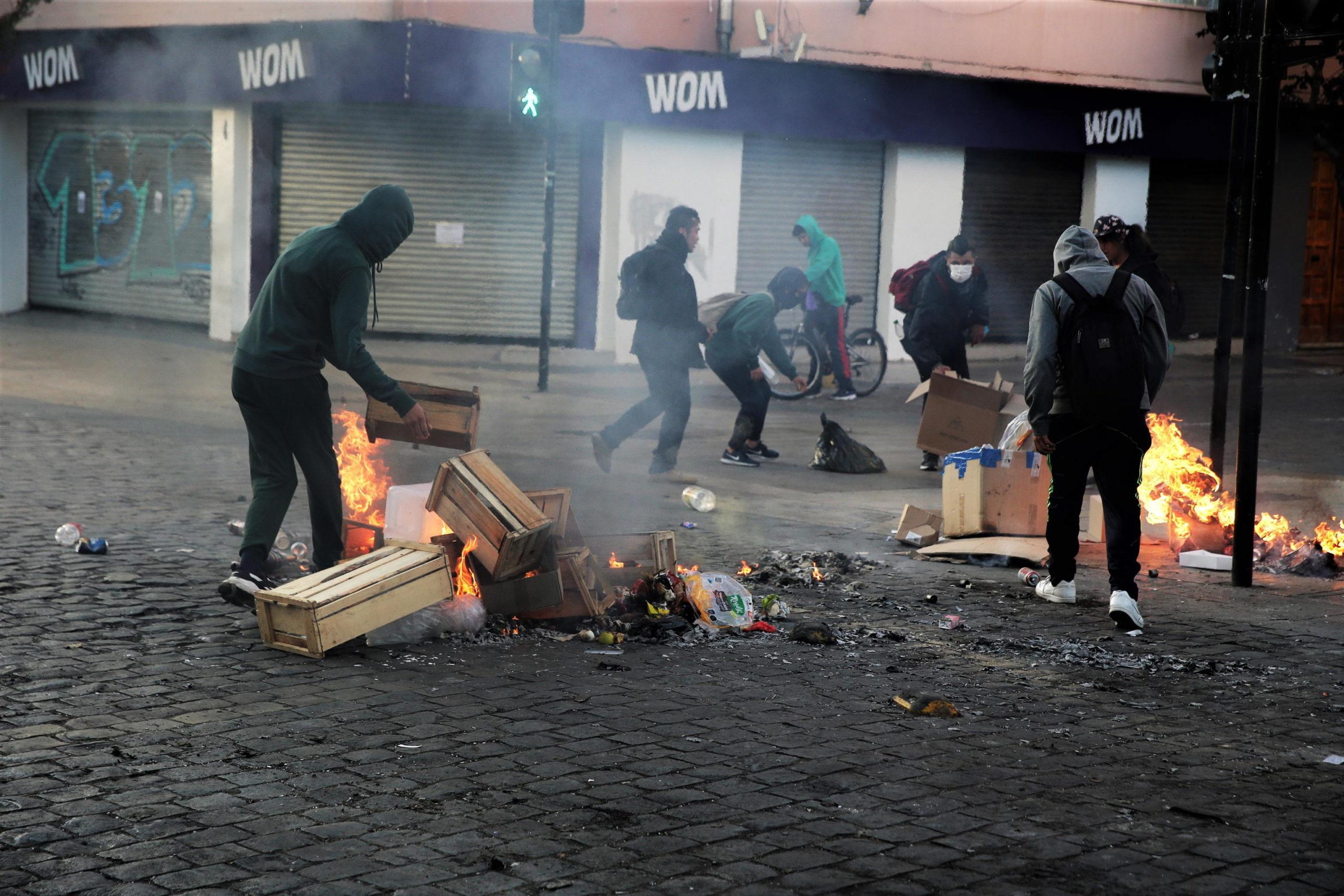 Cittadini in rivolta danno fuoco a casse di legno e altri oggetti