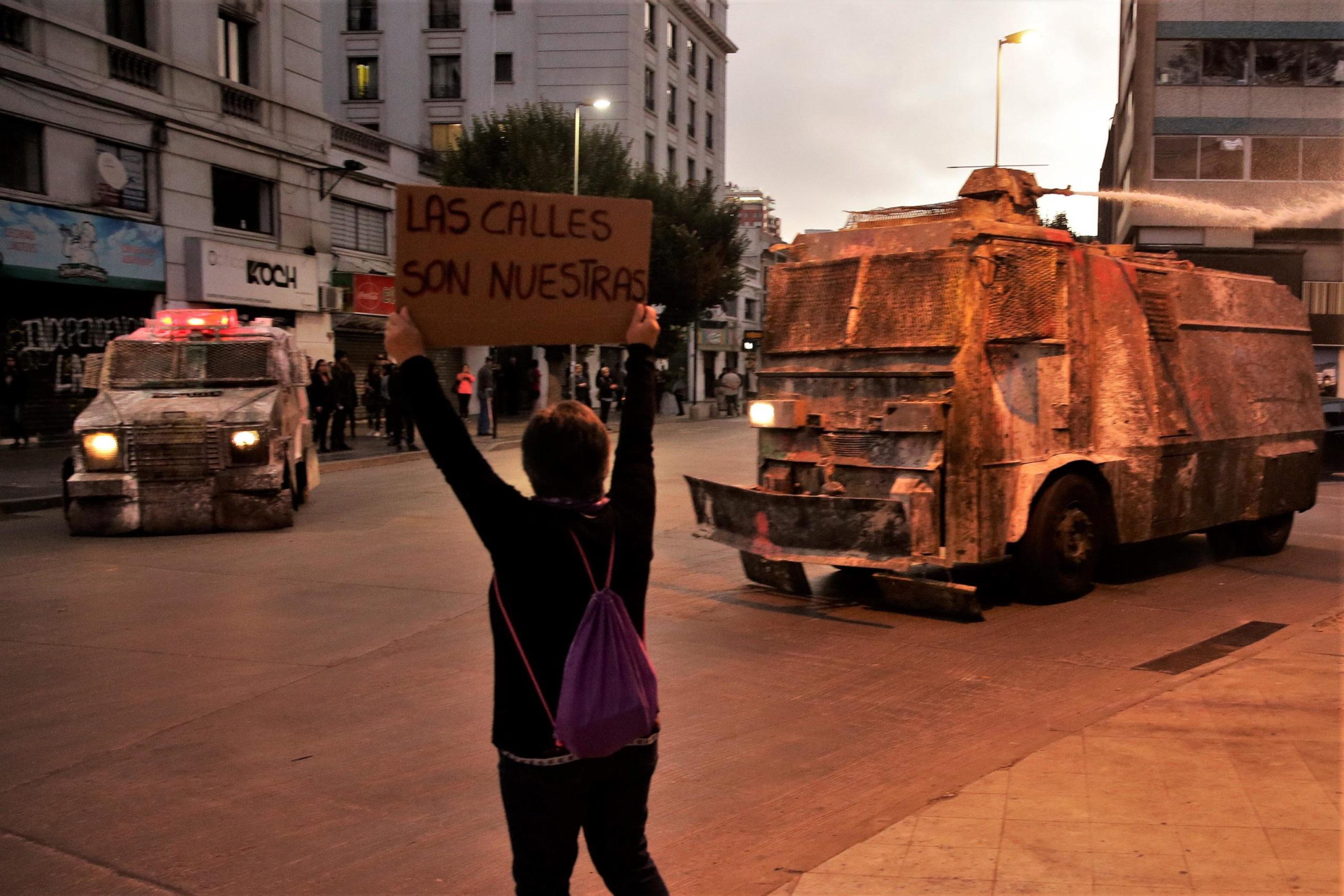 """Un manifestante espone un cartello contro i blindati della polizia: """"Le strade sono nostre"""""""