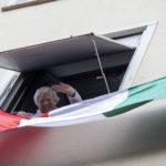 Una donna affacciata alla finestra a Roma saluta i giornalisti