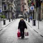 Una donna cammina con i sacchi della spesa nelle strade deserte di Napoli