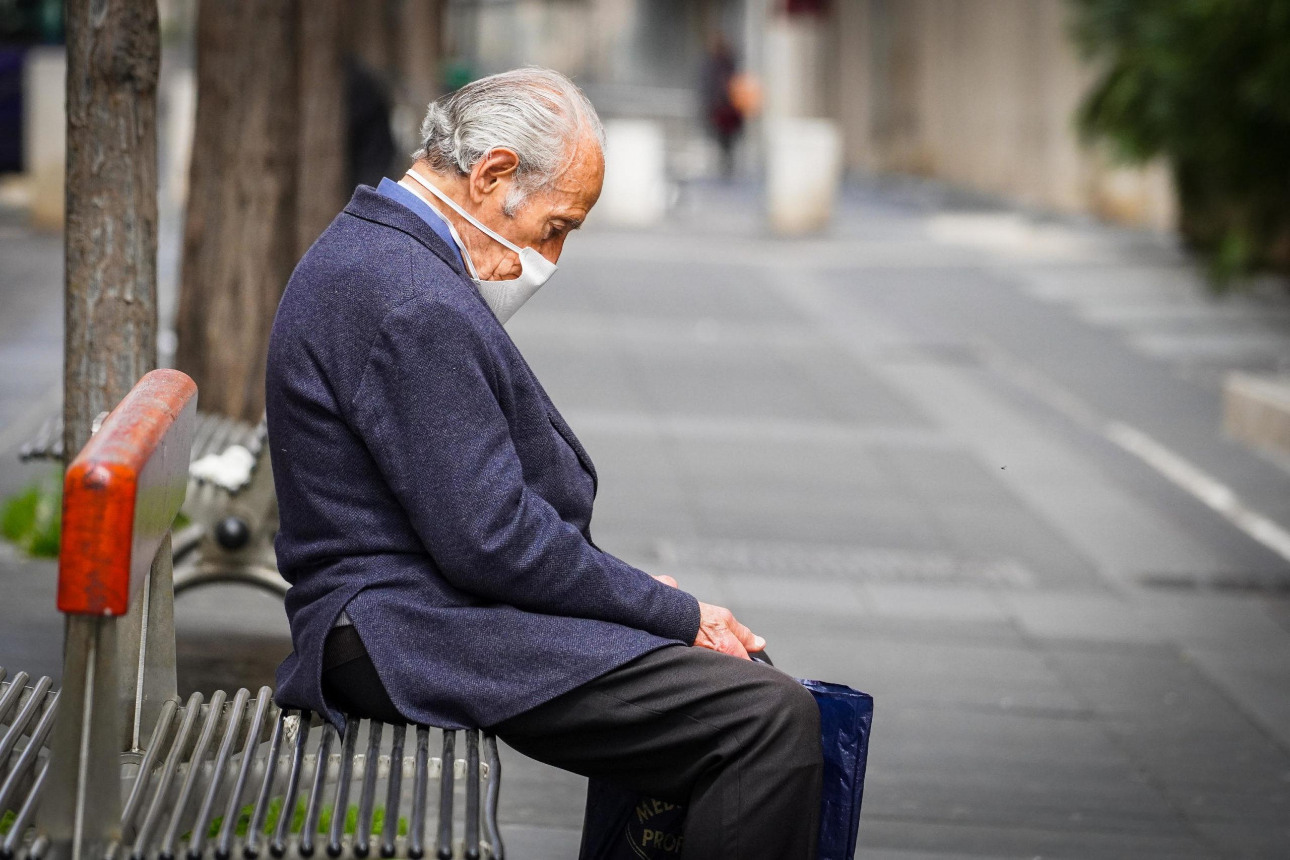 Un uomo con la mascherina seduto su una panchina a Napoli