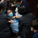 Il deputato pan-democratico Wu Chi-wai viene portato fuori dagli agenti di sicurezza