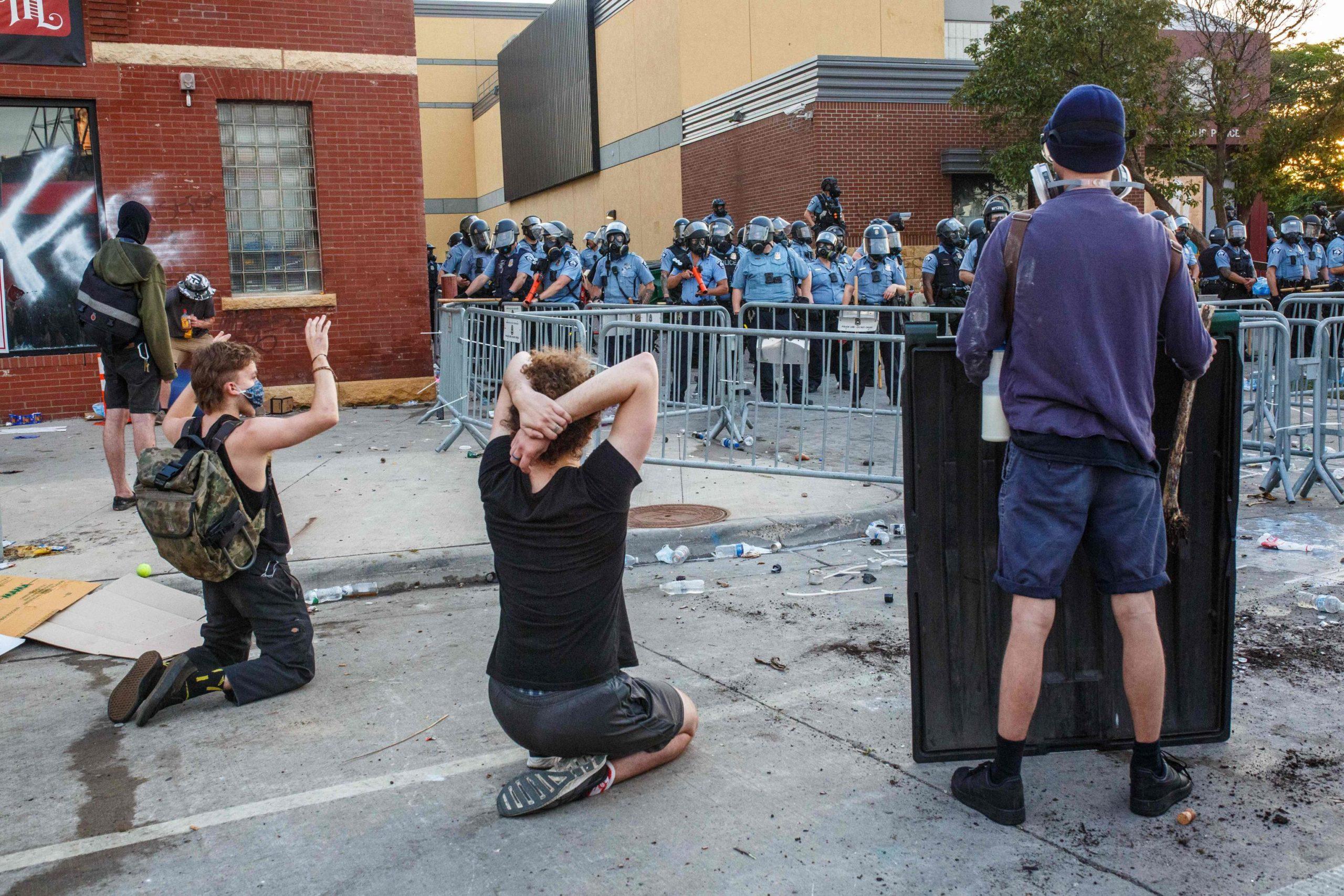 Alcuni manifestanti inginocchiati davanti alla polizia