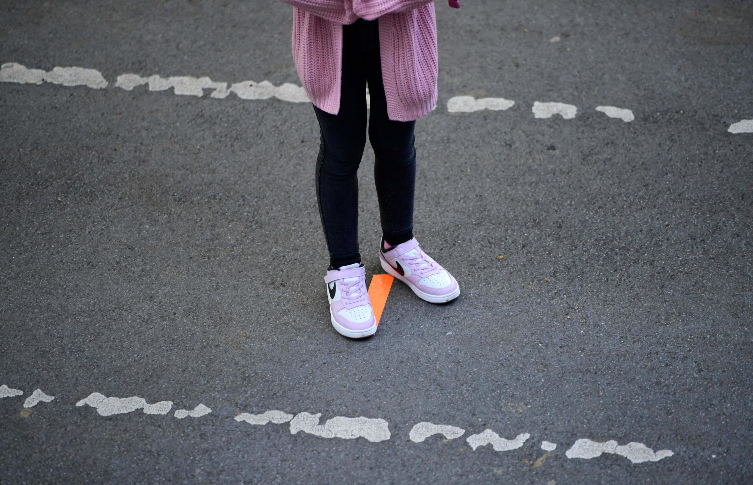 Una bambina sta in piedi sulla linea disegnata per rispettare la fila. Tutti gli alunni sono muniti di mascherine come da protocollo