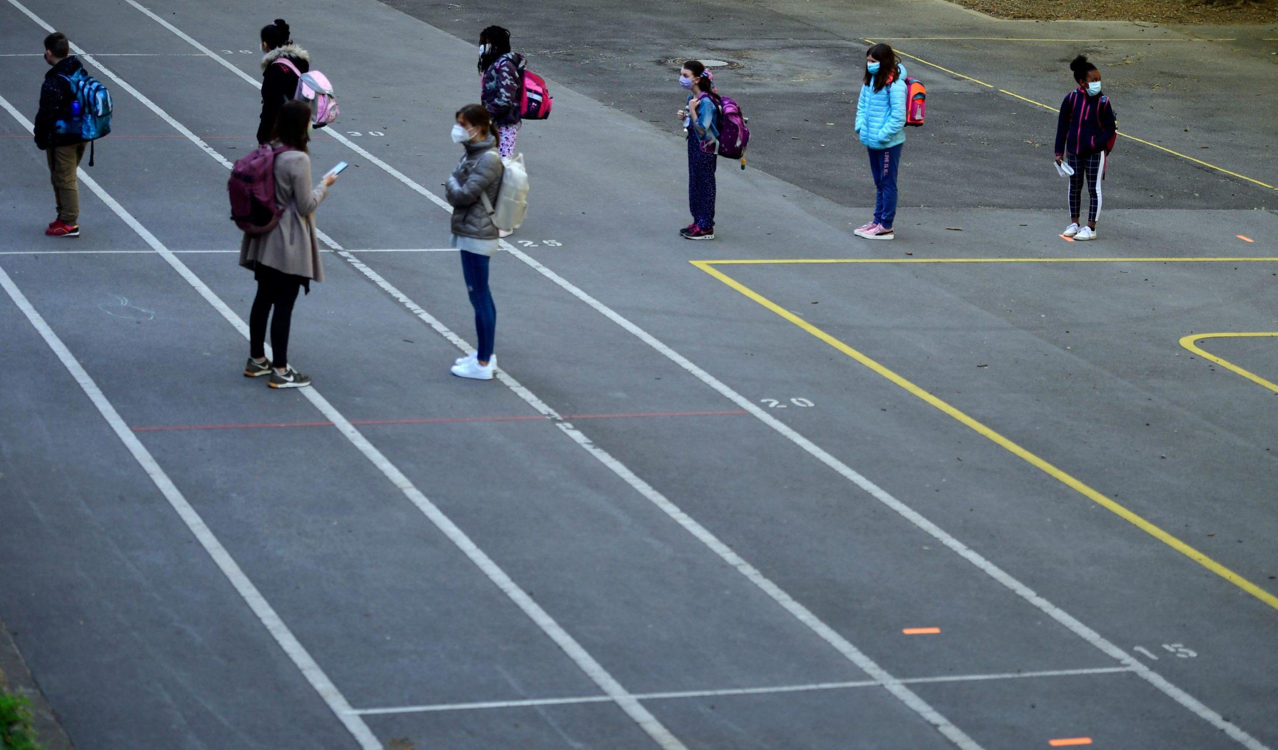 Gli insegnanti forniscono direttive ai bambini riguardo distanze di sicurezza e altre regole da seguire una volta entrati in classe
