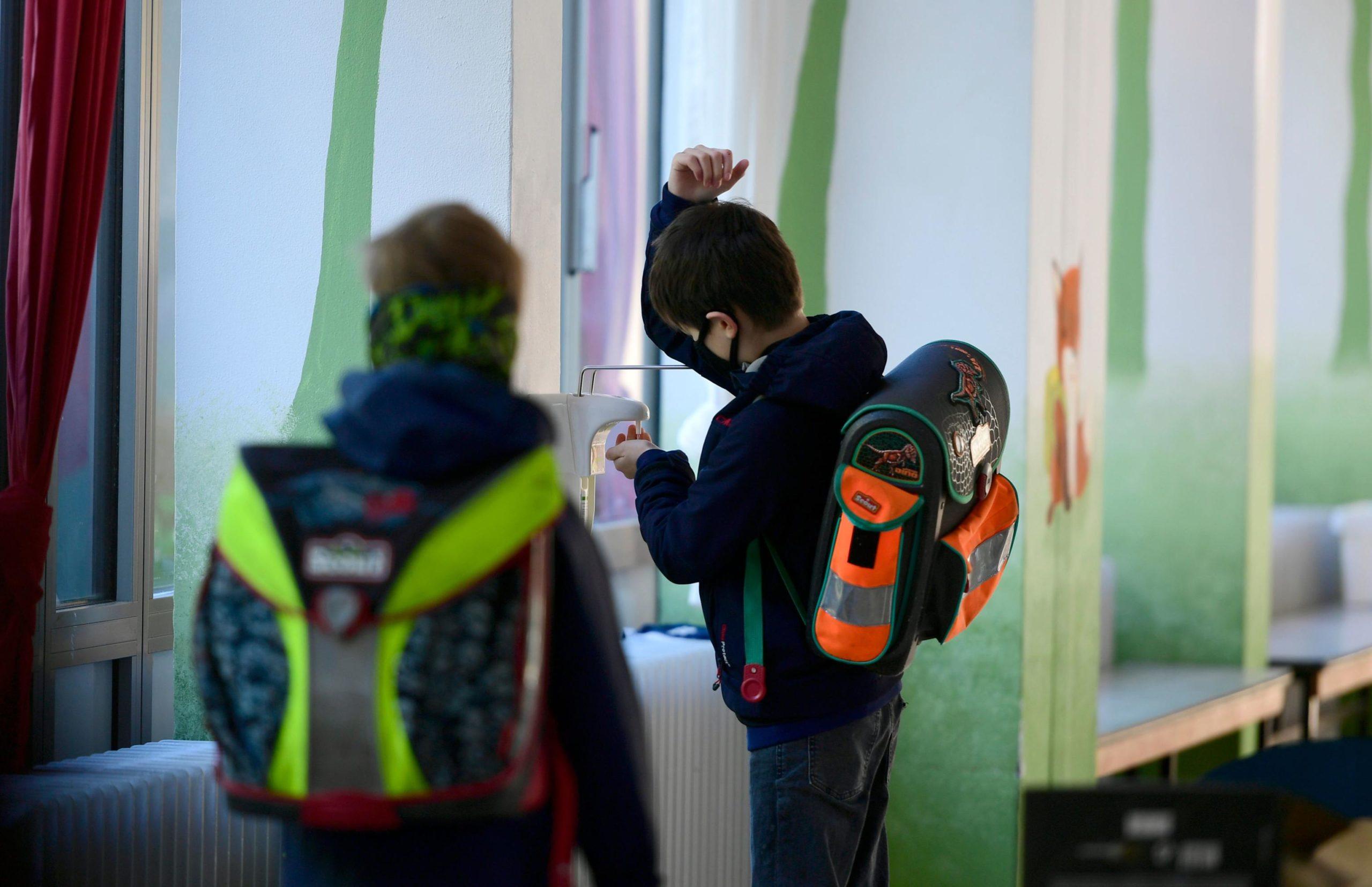 Un bambino si disinfetta le mani, in attesa di dirigersi in aula per le lezioni. Indossa la mascherina come tutti i suoi compagni