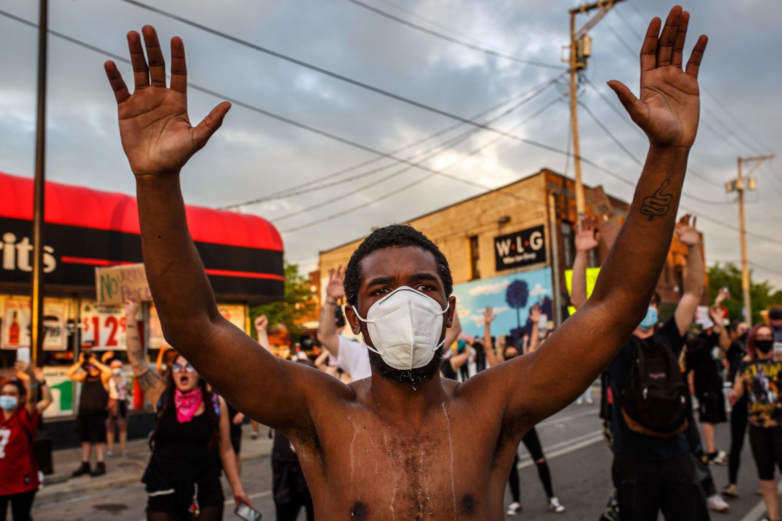 Un ragazzo protesta indossando la mascherina