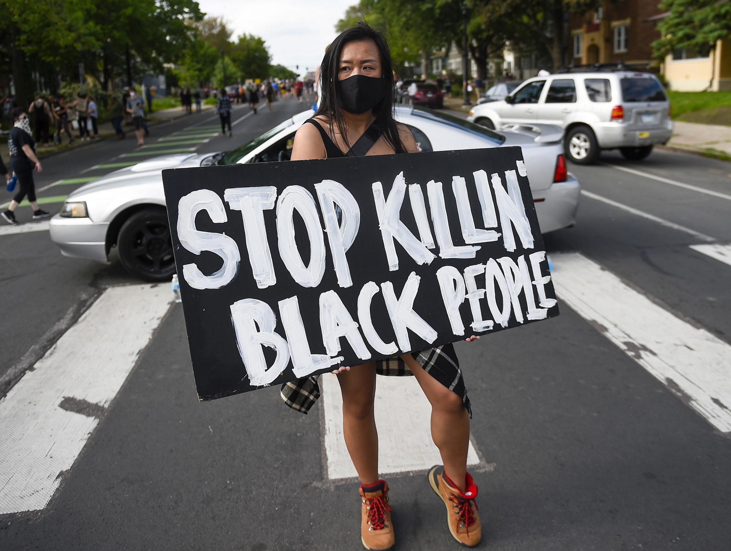 """Una ragazza espone un cartello: """"Smettetela di uccidere le persone di colore"""""""