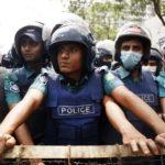 Gli agenti di polizia osservano dietro una barricata gli studenti