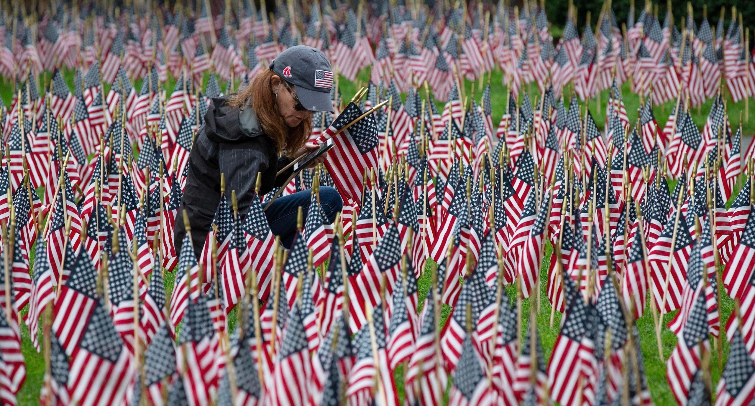 Una donna posiziona una bandiera americana in un giardino commemorativo