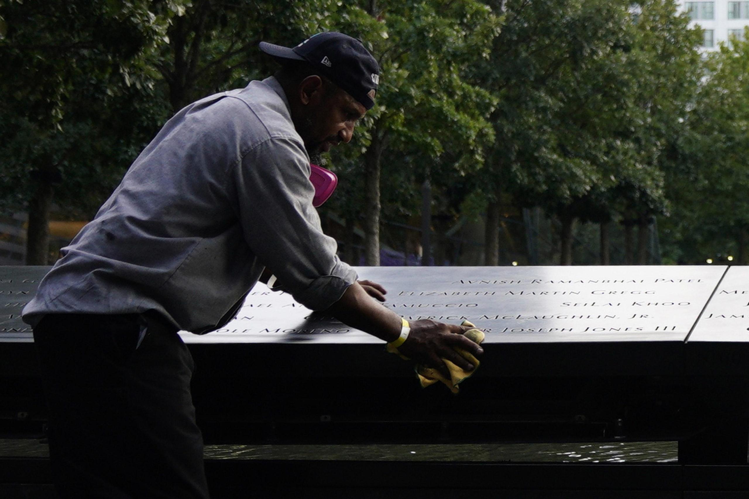 Un inserviente pulisce le targhe attorno alle fontane commemorative dell'11 settembre a New York