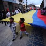 Bambini reggono la bandiera dell'Ecuador nel corteo di protesta