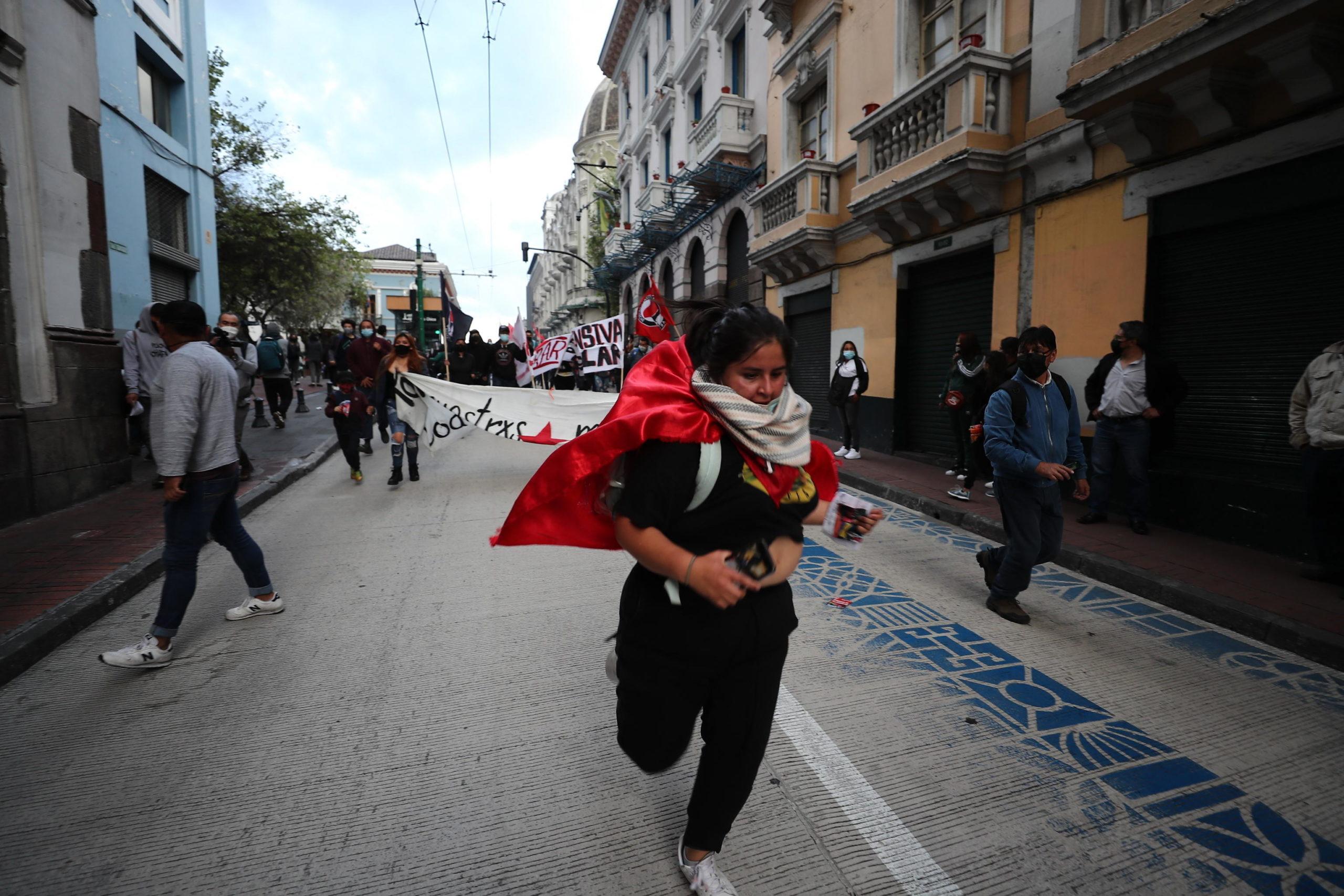 Una donna fugge dalle cariche della polizia